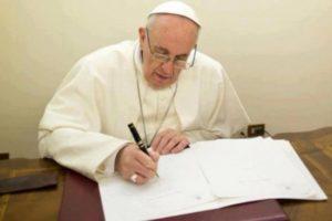 Papa Francesco mentre scrive